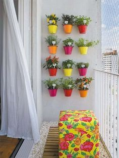 plants on a patio - use Stick Up hangers for small pots on plastic fence divider to hold - Cute!