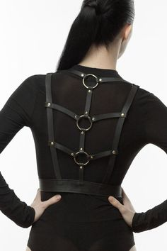 Leather harness features straps detail at back with accents O-rings. Shoulder…