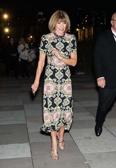 Anna Wintour wears a geometric patterned black and pink dress.