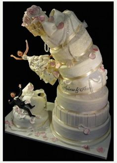 Funny wedding cake made to look as if it's toppling over… bride and groom are falling off the cake, and the top tier is down ... great sense of humor