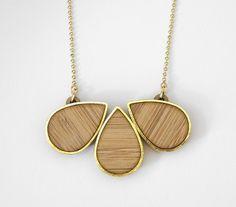 Collier en bambou, cerné de métal doré. Les petites découpes.