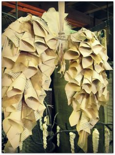 A different take on Angel Wings :: I like this much more than plastic spoons, or paper plates, etc. Plus, fabric rolled like these book pages might look this good, and would drape even better!