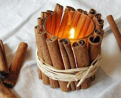 short cinnamon sticks wrapped w/raffia around votive candle in glass holder
