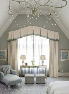 This inverted pleat valance is shaped to follow the arch of the window, and then move out to complement the stationary side panels.