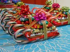 "Candy Cane Sleigh*First you glue a kitkat bar to two candy canes to create the base. Next, attach 10 mini hershey bars on top, with just a drop of glue for each. You stack them in a pyramid, first 4, then 3, then 2, then 1.  After all the glue is hard and secure, glue ribbon around your ""packages"" and a bow on the top. That's it! So cute!"
