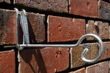 Planter hanger hook for brick walls.  Hang pot plants, hanging baskets, windchimes, ornaments, clocks.  Use two together to make a shelf for your brick wall.