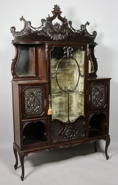 Late Victorian Carved Dark Mahogany Display/Side Cabinet, The Molded Cornice Above A Glazed Cupboard Door With Ribbon Tired Oval Central Panels And Blind Fret Lattice Work Panel To The Base, Enclosing A Pale Green Plush Lined Interior, Flanked By A Pair Of Open Shelves With Shaped Bevel Edge Mirrors To The Back,