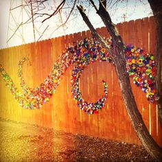 Very fun outdoor art! Plastic caps on wood fence in wave shape. Don't know that…