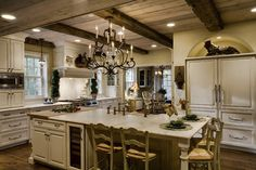 Love, Love, Love - A passion for antiques is reflected in this warm, elegant kitchen. Its centerpiece, a glass-doored antique cabinet. Vintage items include ceiling beams crafted of reclaimed barn siding from a nearby farm & distressed white oak flooring. Simple, yet sophisticated, Carrara marble countertops & subway tiles put the spotlight on the unique collections. Built-in wall nooks & glass-doored cabinetry provide ample room for storing treasured objects.