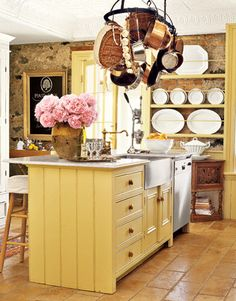 Hanging from the original tin ceiling, a Pottery Barn rack holds kitchen essentials: garlic bulbs, antique copper vessels, and cookware by All-Clad.