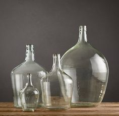 VINTAGE DEMIJOHN BOTTLES  When they were crafted nearly a century ago, our hand-blown demijohn bottles brought locally made wines and fruit brandies to villages across Eastern Europe. Discovered in a village warehouse, they emerged from history as rustic decorative accents for home or garden. Subtle variations in shape and proportion, colors that range from clear to green, and delicate textures and bubbles make each bottle one of a kind.
