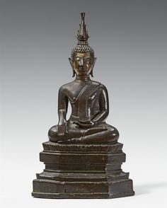 A Chiang San bronze figure of Shakyamuni maravijaya. 15th/16th century A Chiang San bronze figure of Shakyamuni maravijaya seated in meditation (paryankasana) on a lotus above a stepped base, the left hand in bhumisparsha mudra, the left hand in dhyana mudra, the ketumala is inserted into the ushnisha. Remains of gilding to the face. 15th/16th century. Height 30 cm