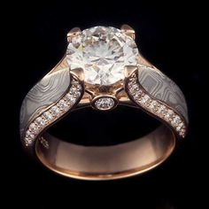This Juicy Light Engagement Ring was done in 14k rose gold with a round diamond center stone. The band features our Iced Platinum Mokume Gane with white diamond accents.