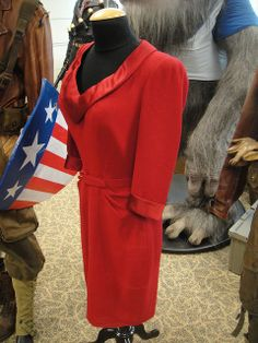 Peggy's red dress on display at a prop auction. You can also see Steve's USO shield behind it.