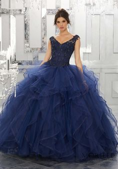 Dramatic and Elegant, This Navy Quinceañera Ballgown Beautifully Combines an Intricate Lace Bodice Featuring Off-the-Shoulder Cap Sleeves. The Full Flounced Skirt is Trimmed in Horsehair. Matching Stole Included. Corset Back. Colors Available: White, Bahama Blue, Bubble, Navy. Princess Sweet 15 Dress by Valencia   Morilee by Madeline Gardner. Style 60026.