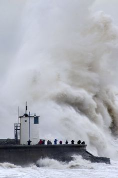 People look on as waves break over the harbour wall at Porthcawl in Wales.