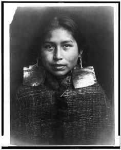 Kwagu'ł girl, Margaret Frank (née Wilson) wearing abalone shell earrings. Abalone shell earrings were a sign of nobility and only worn by members of this class. | Original title: Tsawatenok girl, head-and-shoulders portrait, facing front, Edward S. Curtis, 1914