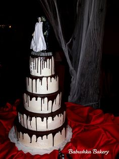 A delicious ganache dripping wedding cake; 2 layers of Red Velvet with Cream Cheese Buttercream and 3 tiers of Chocolate Fudge Cake with Cookies and Cream Buttercream.  The Bride of Frankenstein cake topper is a statue purchased by the bride.