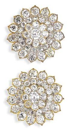 AN EXQUISITE PAIR OF ANTIQUE DIAMOND BROOCHES   Each designed as a rosette centering upon an old mine-cut diamond within a two-tiered old mine-cut diamond surround, mounted in silver and gold, circa 1860
