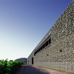 Dominus Winery: Location: Yountville, Napa Valley, California, USAYear of Construction: 1998Architects: Herzog & de Meuron Natural light is able to pass through the gabion walls, that are filled with basalt rocks found locally, to illuminate the interior.