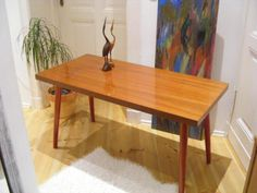 Miracle Pretty coffee table with elegant red feet of wood. Good condition.  Dimensions: width: 130 cm height: 57 cm depth: 47 cm
