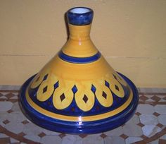 Tagine describes both the food and the cooking vessel. A two part tagine vessel is traditionally a shallow, round glazed earthenware base covered with a tall conical lid made of the same material. The tagine is meant to be used over fire (though flames should not touch the base) or on the top of the stove over medium to low heat. The conical lid traps the steam, keeping the heat moist. The shape of the vessel helps circulate the heat. The tagine is easy to make at home
