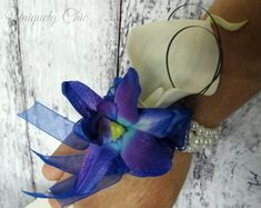 This little beauty is a perfect accent for the upcoming grads. A real touch white calla lily with a silk blue, purple, turquoise galaxy orchid, finished off with sheer ribbon bows and trailers and set on a bracelet of your choice.  #realtouchcalla #callalilycorsage #wristcorsage #realtouchcorsage #blueorchidcorsage #blue #white #accessories #weddings #etsy #galaxyorchid #bluepurpleorchid