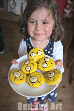 Despicable me cupcakes and one HAPPY girl!!! We can't decide which is cuter: the cupcake or the little girl holding them!