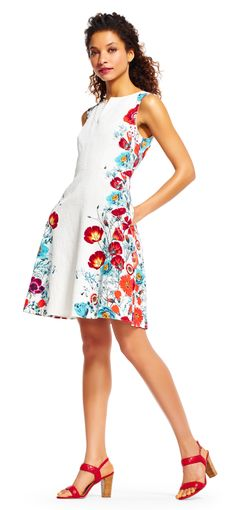 Flirty and bright, this chic fit and flare dress is the perfect look for every day. This skater dress features floral prints accenting each side contrasting the simple styling of the rest of the look. A notched neck and full skirt complete the style. Paired with a bold heel to bring out the floral accents, this dress is easily styled from day to night.