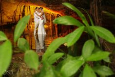Newlyweds in a cenote cave in the Riviera Maya for a trash the dress shoot. Mexico wedding photographers Del Sol Photography.