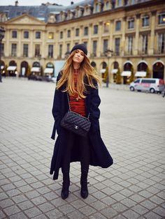 Kristina Bazan of Kayture in a red high neck shirt under a long black coat with a black beanie