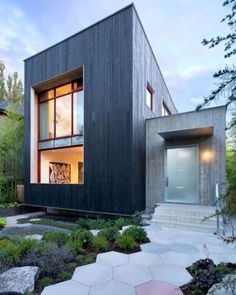 Modern house designed by Measured Architecture in Vancouver Canada. The exterior of the home is covered in carbonized cypress wood exterior cladding giving it a bold and dark appearance. image Latreille Delage Photography Ema Peter Photography and Martin
