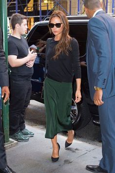 Victoria Beckham in a black sweater + emerald green midi skirt + black heels