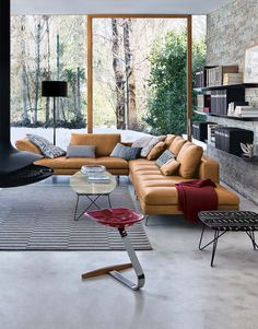 modern leather sofa in tobacco color, concrete floor, rough stone wall