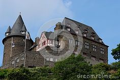 Photo taken in a center called Bacharach along the Rhine valley in Germany. In the picture you see his side fully intact castle, especially on the left you see the high circular tower from the tip cone delineated by blue sky. To the right you see the very massive housing part and center the facade of a typical house of the place with wooden logs in the wall.