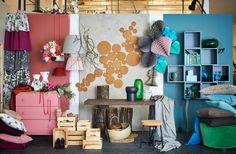 Ein Arrangement aus einer rosafarbenen Kommode, Stoff mit Blumenmuster, Korkuntersetzern und Möbeln. Hinzu türkisfarbene Kissen und Wandschränke.
