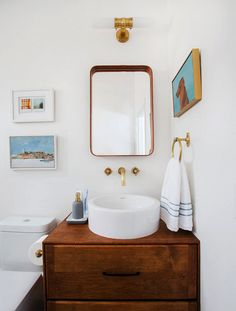 Small, nautical inspired bathroom with a wooden mirror, a wood vanity, and gold accents