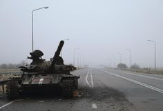 A destroyed tank is seen along a road in the territory controlled by the self-proclaimed Luhansk People's Republic near the airport in Luhansk, November 19, 2014.