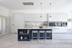 Our luxury coastal design features a striking kitchen island along with handle-less furniture and a wealth of functional storage spaces throughout.