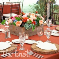 Wooden chargers (cut from a fallen tree) and burnt orange linens.  Also love the flower box.