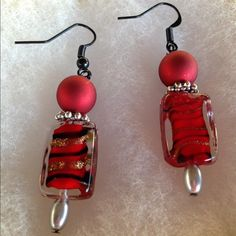 Unique swirled glass dangle earrings These handmade earrings feature lovely red glass beads with black and gold swirls. These are small and lightweight. Elegant, classy look to jazz up any outfit! Jewelry Earrings