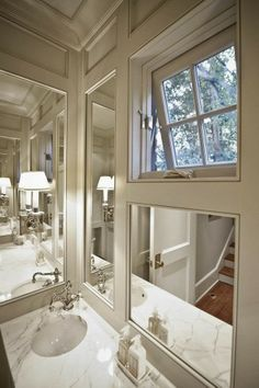 mirrors set into paneling in a bathroom is so european... so nice