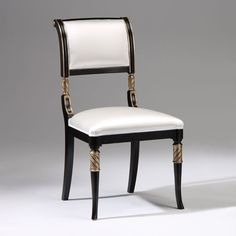 Regency style carved beechwood chair in antiqued black finish with antiqued silverleaf trim and off-white upholstery; Made in Italy.