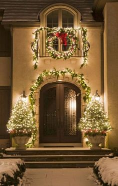 Small potted trees frame the doorway and, when lit, add to the Christmas cheer on the front stoop. - Traditional Home / Photo: Courtesy of Mariani Landscape