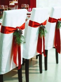 Christmas Table Ideas Using Red and White: Give your dining room chairs a festive touch by wrapping them with wide red satin ribbon and adding some greenery.