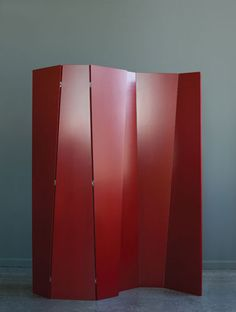 """Atlas Industries: The folding screen comprises three hinged panels, without a designated top or bottom. They can be used singly, or in combination, to form a variety of undulating patterns; a sculptural yet functional addition to the home or office. In this image, two screens are shown.    This first version of the folding screen measures 72"""" x 40"""", and has a red opaque lacquer finish."""