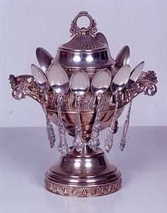 AN AMERICAN SPOONER-COVERED JAR in chased and engraved silver plate with ringed finial-handle. Fitted with eleven sterling silver tea spoons with chased and engraved handles. Height 10 in.  http://www.ogallerie.com/auctions