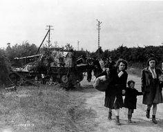 Réfugiés sur la route Montebourg-Sainte-Mère-Eglise, en arrière plan un 7,5 cm Pak 40/41 1 ausf Geschutzwagen Lorraine Schlepper SdKfz 135, plus connu sous le nom de Marder!