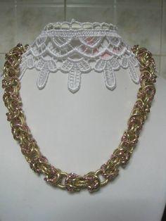 Collana a catena lavorata a mano, pezzo raro, con anelli in alluminio di colore rosa zigrinati e di colore oro lisce e satinate. Chiusura collana con moschettone dorato.Diametro anelli. 1 cm.Lunghezza collana: 44 cm.