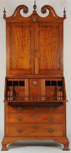 18th century Philadelphia, Pennsylvania mahogany desk and bookcase or secretary. Bookcase top is comprised of pine secondary wood and features a swan's-neck pediment, carved rosettes, and applied carved shell, above hinged scallop-paneled doors opening to three shelves over two lower candle slides. Desk is comprised of mainly poplar secondary wood and exhibits blind dovetail top construction. The fitted interior features upper pigeon hole drawers with molded fronts